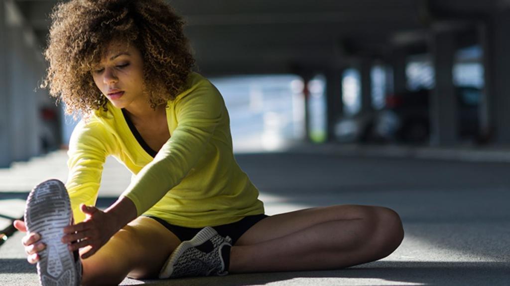 Девушка тянет ногу на улице