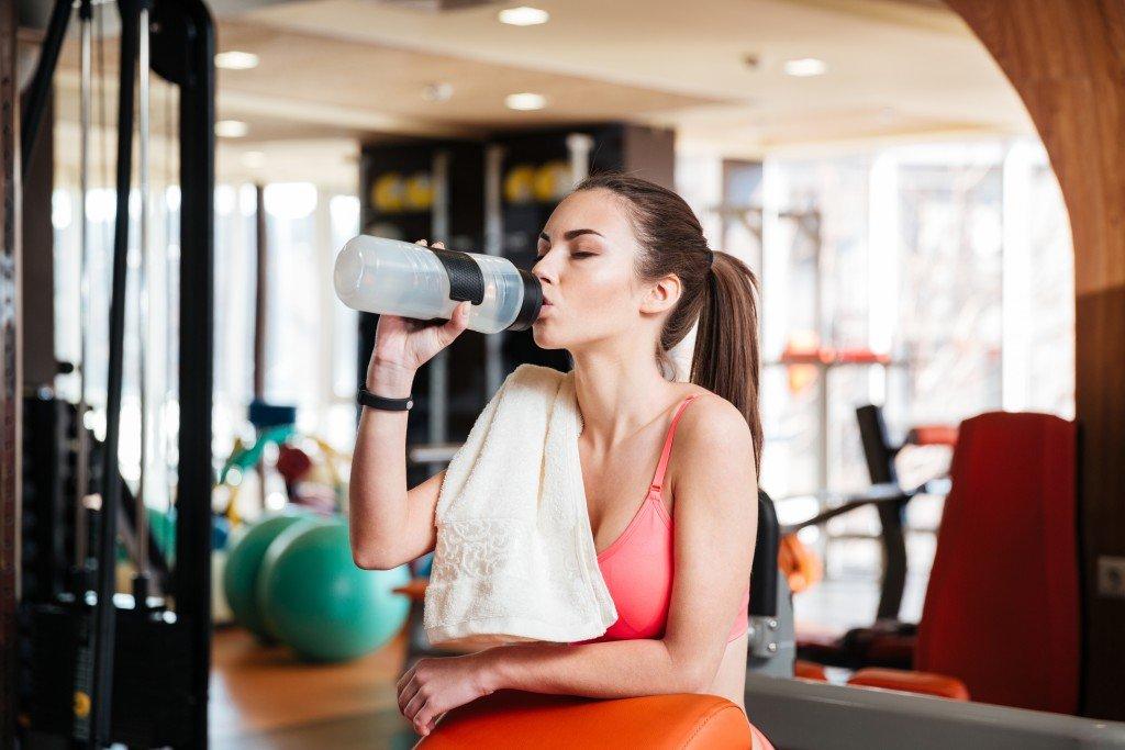 Девушка на тренировке пьет воду