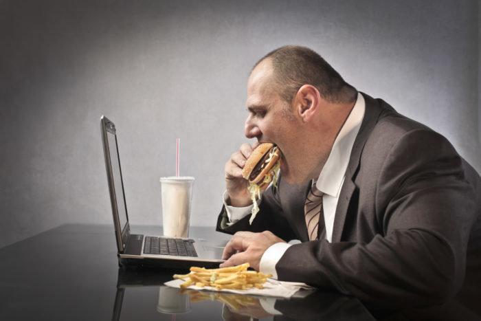 толстый человек ест фаст-фуд